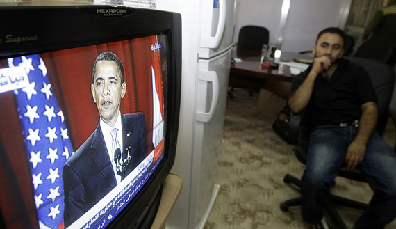 A resident watches a television broadcasting the speech of U.S. President Barack Obama, at Culture Ministry in Baghdad
