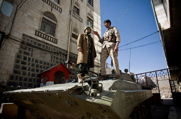 Houthis on Thursday atop an armored vehicle, which had been seized outside the house of President Abdu Rabbu Mansour Hadi in Sana, Yemen. Photo Credit: Hani Mohammed/Associated Press