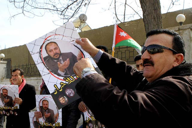 Supports of Zaki Bani Ersheid, hold photos of him, outside the state security court in Amman, Jordan, Sunday, Feb. 15, 2015. Photo Credit: AP/Raad Adayleh