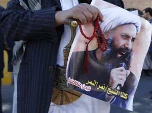 Shi'ite protester carries a poster of Sheikh Nimr al-Nimr during a demonstration outside the Saudi embassy in Sanaa