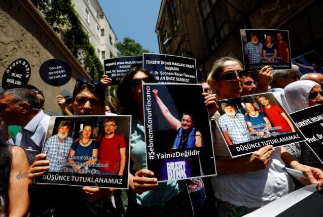 Demonstrators hold pictures of Nesin, Fincanci and Onderoglu during a protest against arrest of the three prominent campaigners for press freedom, in front of the pro-Kurdish Ozgur Gundem newspaper in central Istanbul