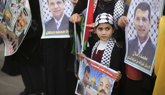 Palestinian supporters of former head of Fatah in Gaza, Mohammed Dahlan, hold posters during a protest against Palestinian President Mahmoud Abbas in Gaza City